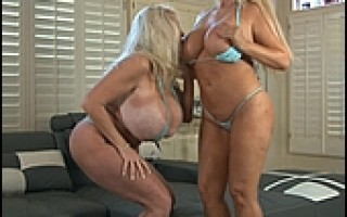 Two big boobed blonde MILF\'s fuck each others shaved pussies with big toys.